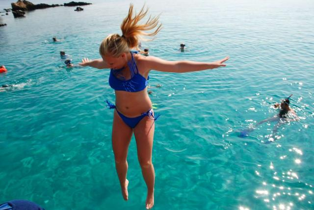 High school traveler jumps into the sea on their summer teen tour to Greece.