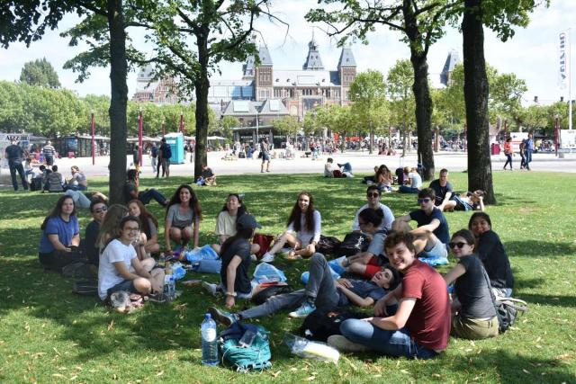 Teenage travelers relax in Amsterdam Vondelpark during summer youth travel program
