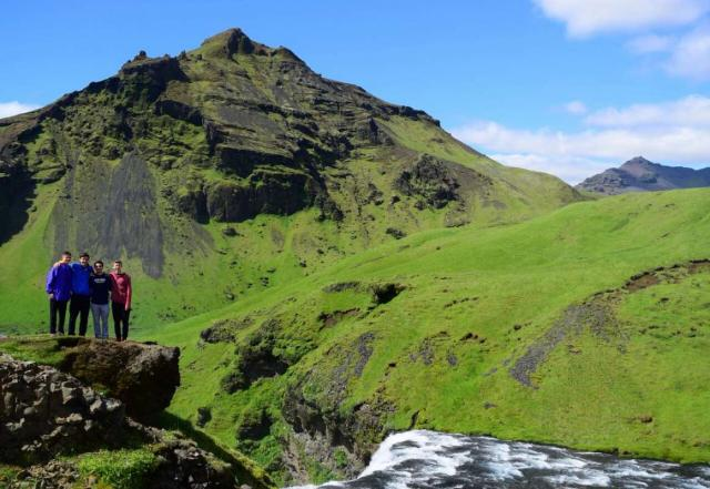 Teen travelers with waterfall and mountain in Iceland on summer adventure travel program