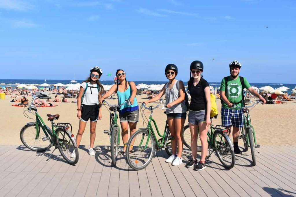 Teenage travelers biking on Barceloneta boardwalk in Barcelona during summer youth travel program