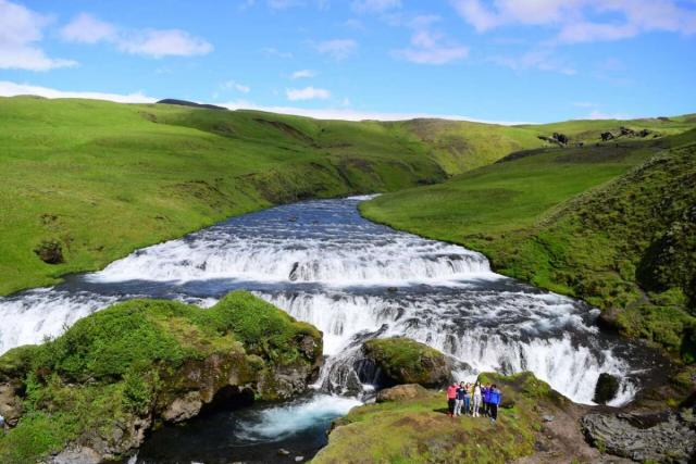 Teen travelers with Iceland waterfall on summer youth adventure program