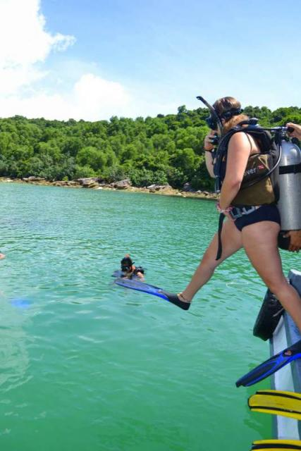 Teenage traveler jumps into the water to go scuba diving during summer youth travel program in Southeast Asia