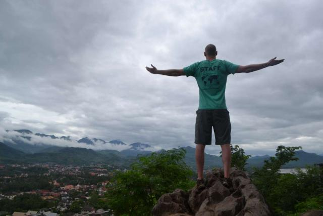 Teen tour camp counselor climbs rocks during summer youth program in Southeast Asia