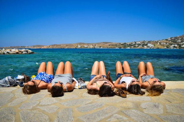 High school travelers relax on the seaside in Greece on their summer teen tour.