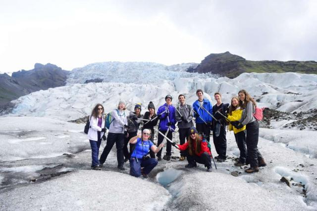 Teen travelers ice climbing glacier on Iceland adventure youth travel program