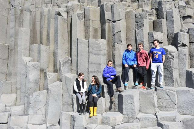 Teen travelers on rock formations in Iceland during youth adventure travel program