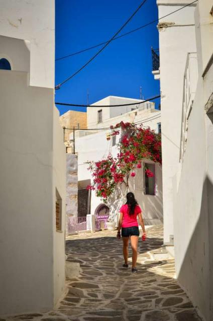 High school student wanders the narrow alleyway in Greece on their summer teen tour.