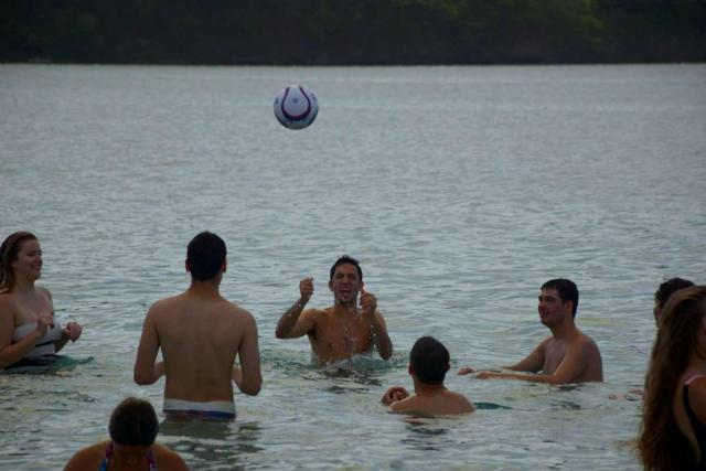 Group of teens enjoys volleyball in the water on summer adventure program in Costa Rica.