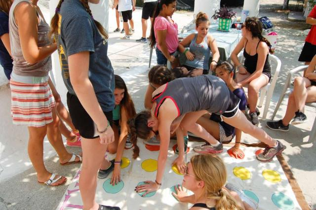 Teenage travelers play Twister with local children during summer youth travel program in Greece
