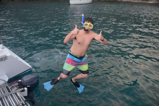 Teen jumps into the water to snorkel on summer adventure program in Costa Rica.