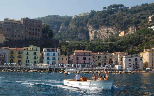 Teenage travelers on private boat cruise of Amalfi Coast during summer youth travel program in Italy