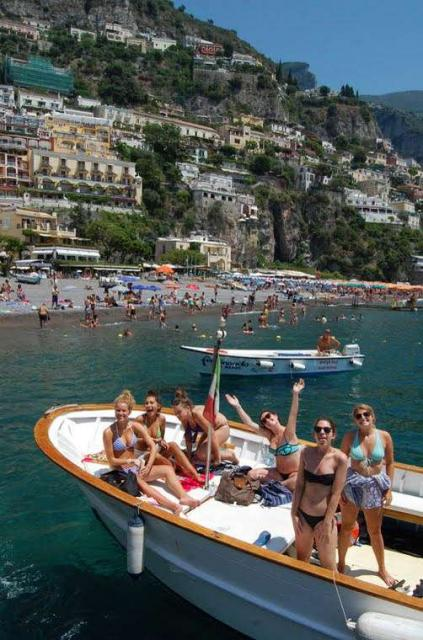 Teenage travelers go on boat cruise in Mediterranean Sea during summer youth travel program in Italy