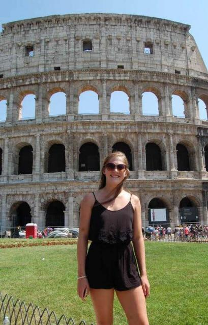 Teenage traveler visits Colosseum in Rome during summer youth travel program in Italy