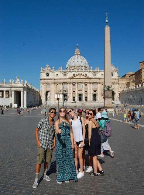 Teenage travelers pose for selfies at Saint Peter's Basilica at the Vatican in Rome during summer youth travel program