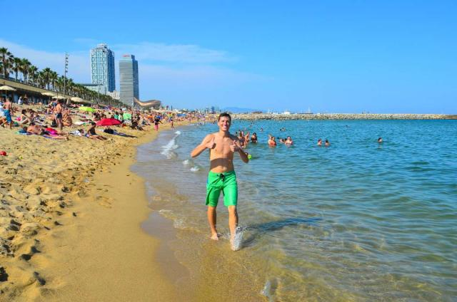Teenage boy traveler on Barcelona beach during summer teen travel program