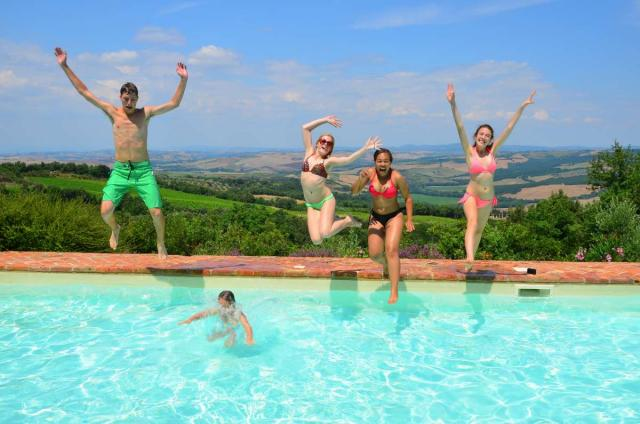 Teenage travelers jumping into pool with Tuscany in background on summer adventure travel program