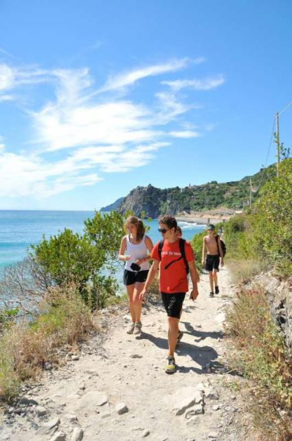Teenage travelers hike Cinque Terre trail during summer adventure travel program