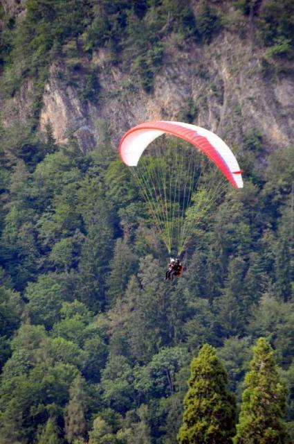 Teenage travelers paraglide in Interlaken during summer teen adventure travel program