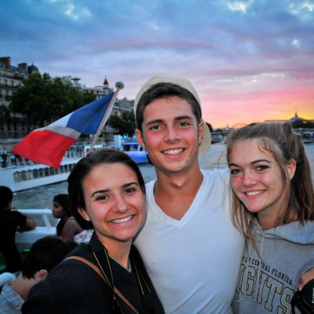 Teenage travelers cruise down River Seine at twilight on summer youth travel program
