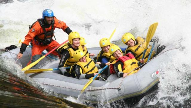 Teenage travelers go whitewater rafting during summer youth travel program in Scandinavia
