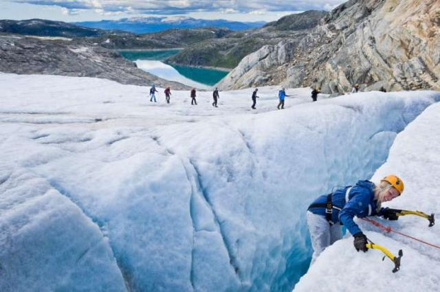 Teenage travelers climb glacier during summer youth travel program in Scandinavia