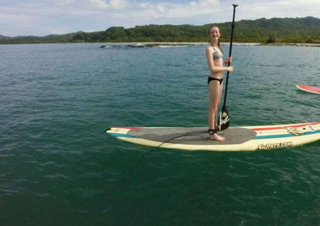 A student learns how to stand-up paddle board on her teen travel tour of Costa Rica.