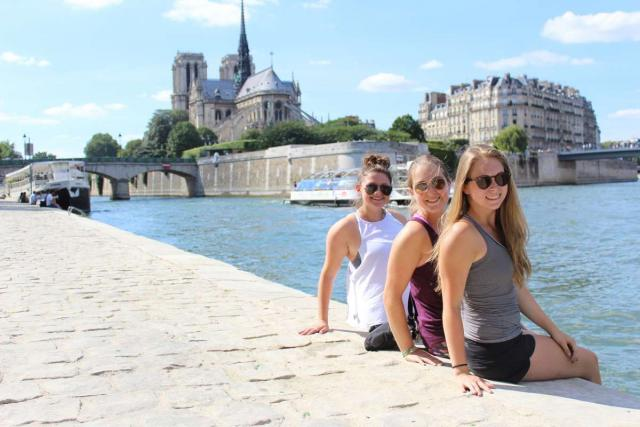 Teenage girls relax by River Seine and Notre Dame on summer youth travel program in Paris