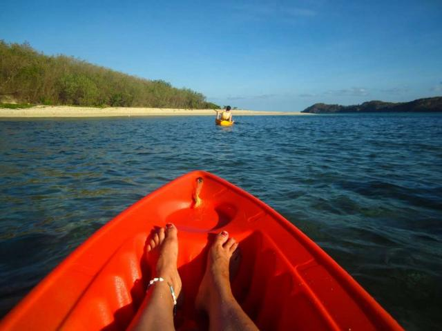 Teenage traveler kayaks through the Pacific Ocean during summer youth program in Fiji