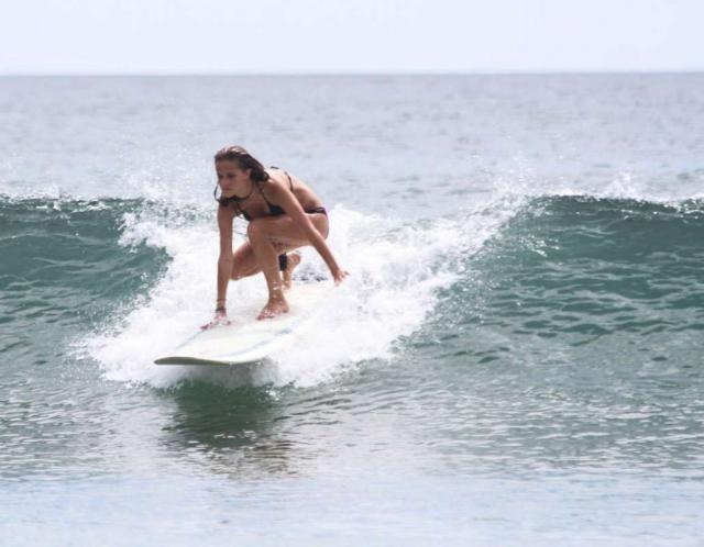 Girl surfs on teen summer program in Costa Rica.