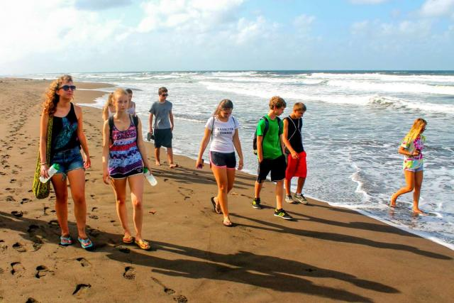 Group of teens do service work on the beach in Costa Rica on summer adventure program.