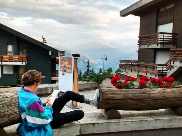 Teen relaxes in Swiss Alps during summer adventure travel program
