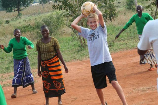Teens participate in games with host students during service program in Tanzania.