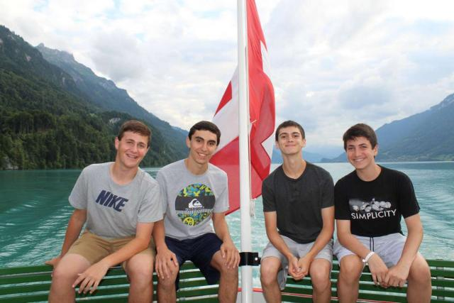 Teenage travelers on lake boat cruise in Switzerland during summer travel program