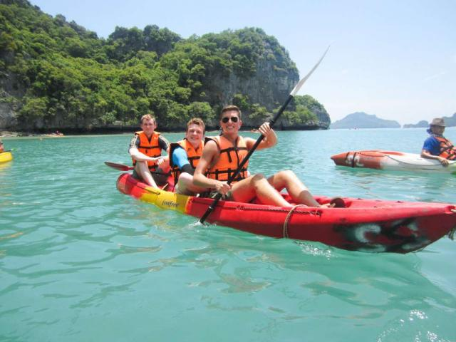 Teenage travelers kayaking in Thai islands during summer youth travel program in Thailand