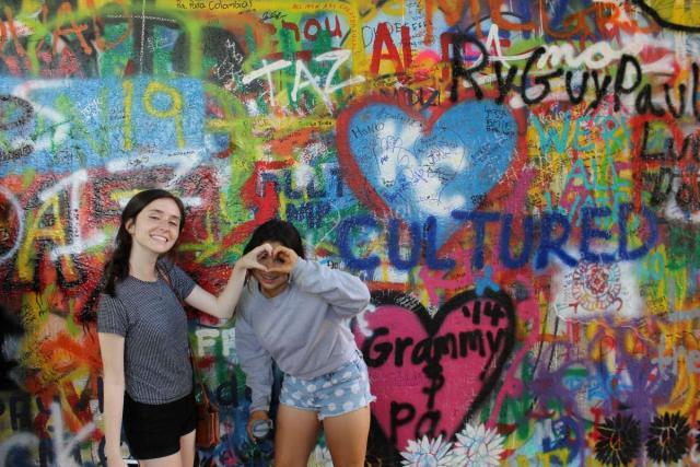 Teenage travelers at John Lennon Wall Prague on summer adventure travel program