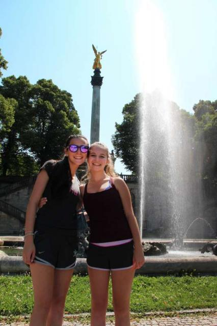 Teenage travelers relax in European park on summer teen tour program
