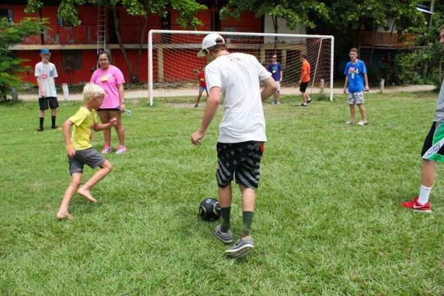 Teens play soccer with local children on summer service program in Costa Rica.