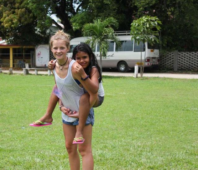 Teen plays with local girl on summer service program in Costa Rica.