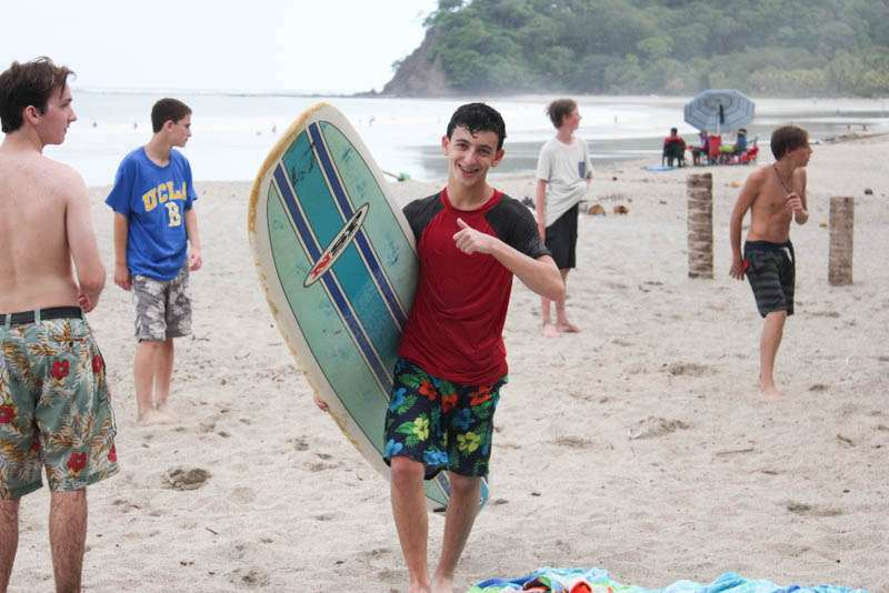 Boys surf and play games on the beach on teen summer travel program in Costa Rica.