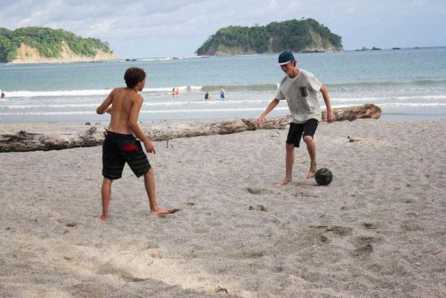Teen boys play soccer on the beach during their summer travel program in Costa Rica.