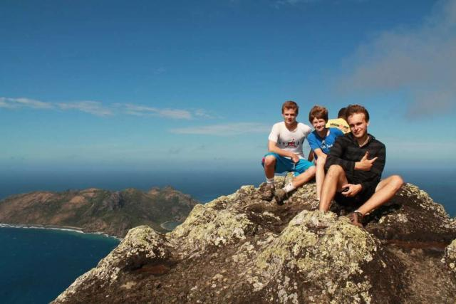 Teenage travelers climb rocks for great views during summer youth program in Fiji