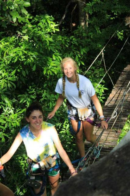 Teens cross rope bridge in the jungles of Costa Rica on summer student adventure program.