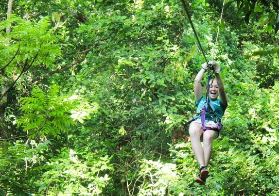 Teens zip-line through the jungle canopy in Costa Rica on summer adventure program.