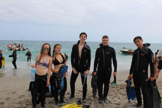Teenage travelers on beach in wetsuits about to go scuba diving in Malaga on summer youth adventure program