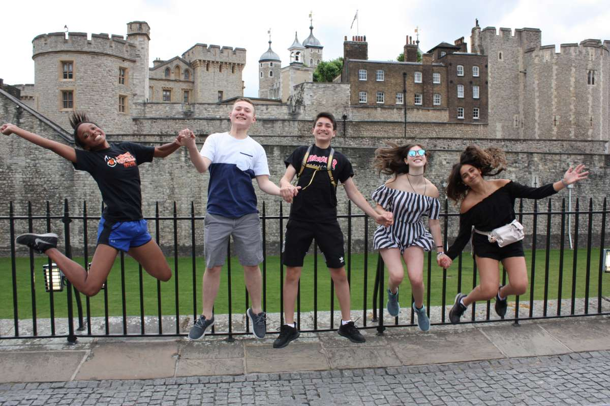 Happy teens jump at Tower of London during summer travel program
