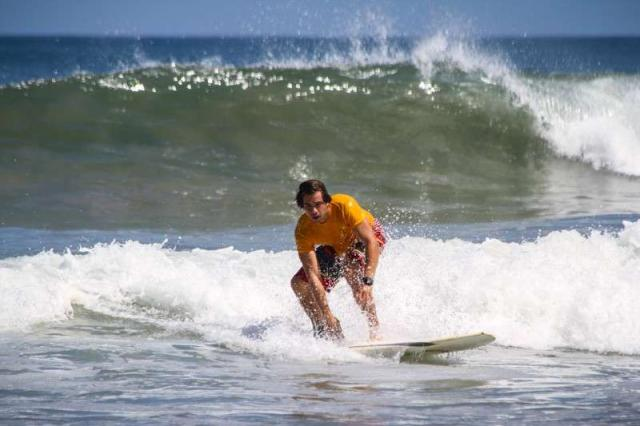 Teen boy surfs in Costa Rica on summer adventure program for students.