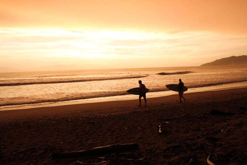 Teens walk the beach before surfing on summer travel program in Costa Rica.
