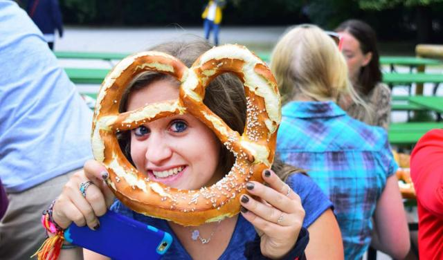 Teenage traveler eats pretzel local authentic traditional Bavarian cuisine during summer youth travel program