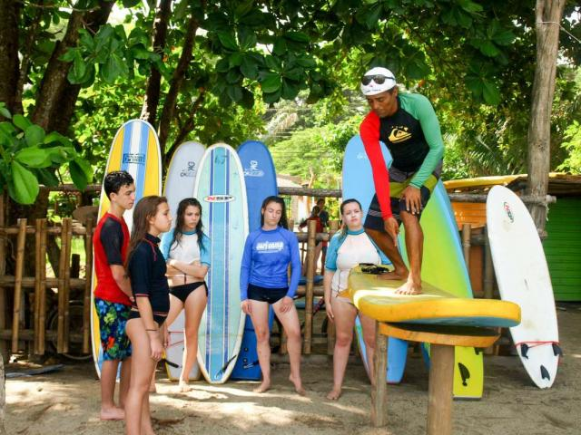 Group of teens learn how to surf on summer travel program in Costa Rica.