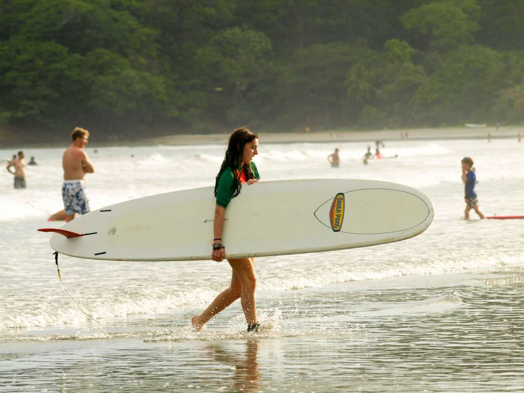 Teen girl takes her surfboard to water on summer student tour in Costa Rica.
